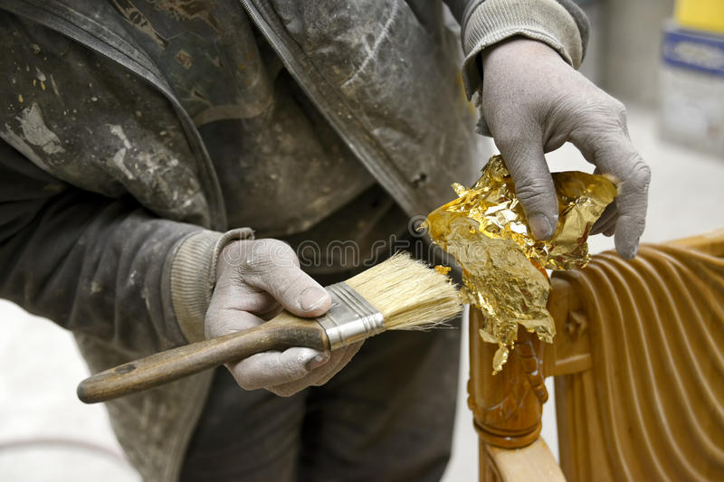 Carpenter. Appyling Golden Leaf To A Furniture stock photo