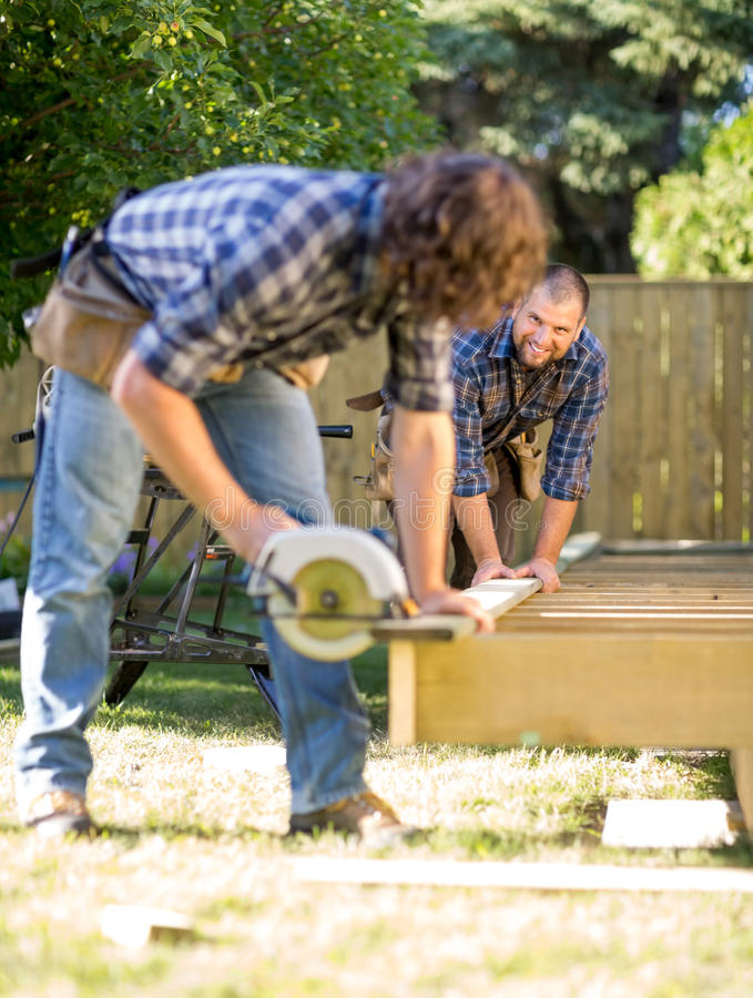 Carpenter Assisting Coworker In Cutting Wood With stock images