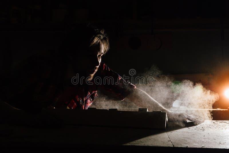 Carpenter blows off wood dust cloud. stock images