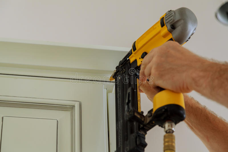 Carpenter brad using nail gun to Crown Moulding on kitchen cabinets framing trim,. With the warning label that all power tools have on them shown illustrating stock photography