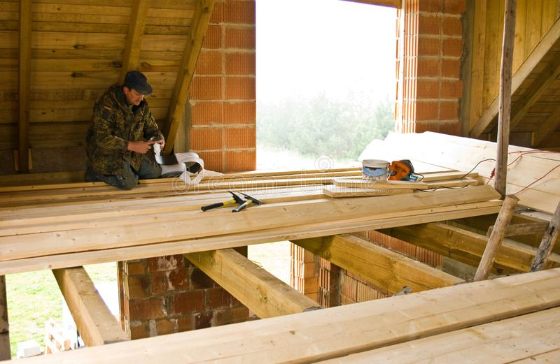 Carpenter building new floor of a loft room royalty free stock images