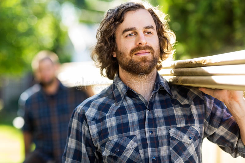 Carpenter Carrying Planks While Looking Away. Mid adult carpenter carrying wooden planks with the help of coworker while looking away stock image