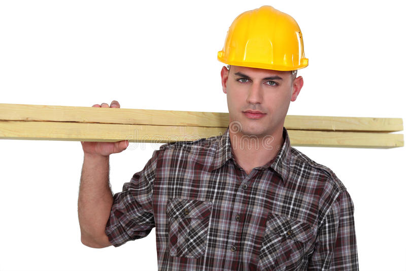 Carpenter carrying planks stock photography