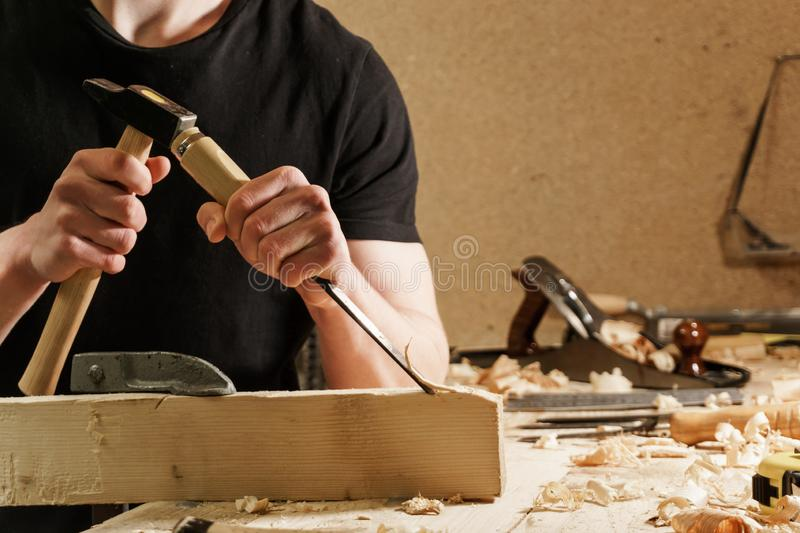 Carpenter carving wood with a chisel stock image