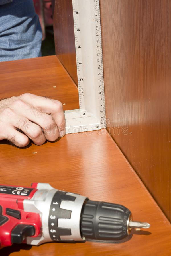 Carpenter checks the angle of joining the furniture boards using the angle bracket. royalty free stock image
