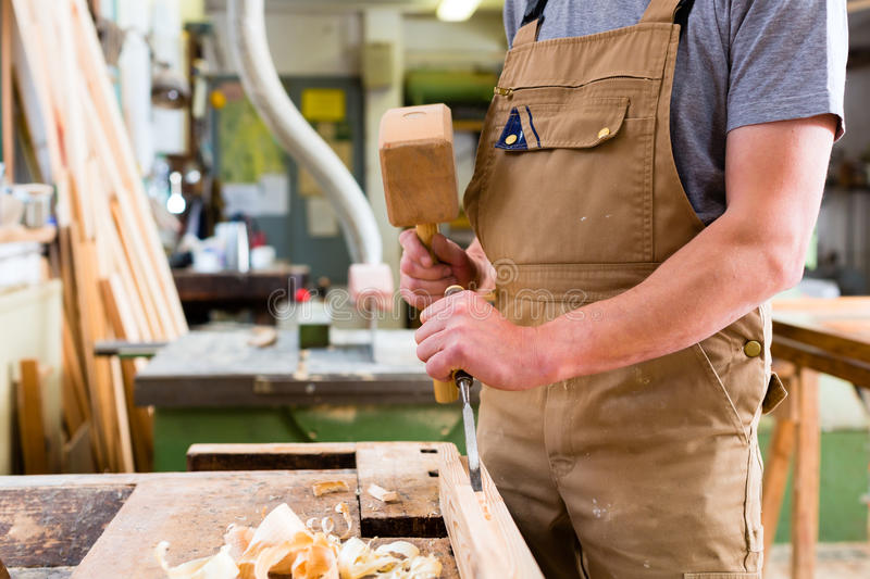 Carpenter with chisel and hammer stock image