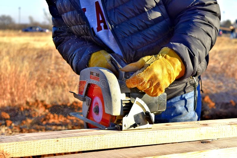 Carpenter with circular saw, cutting boards on site. Carpentry, two by four, outdoor, project royalty free stock images