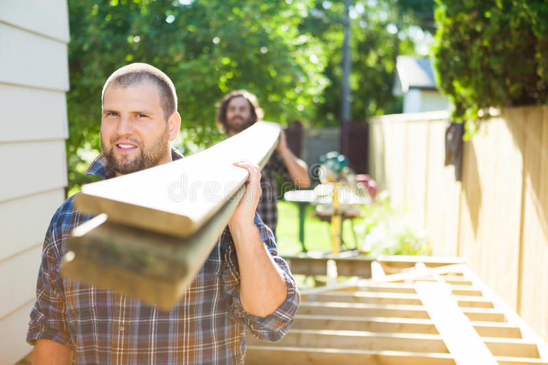 Carpenter And Coworker Carrying Lumbers At stock photos