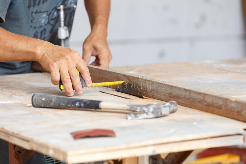 Carpenter cut wood for house construction. A carpenter cut wood for house construction royalty free stock photo