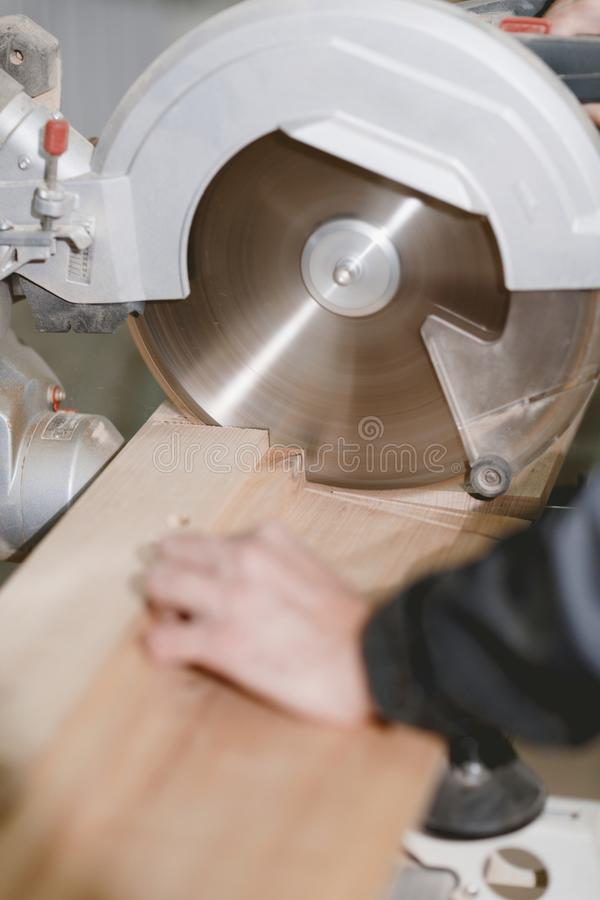 A carpenter cuts a bar of wood on a metal lathe with a sharp round knife for cutting wood. Close-up. stock photography