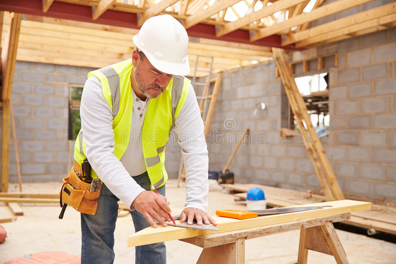Carpenter Cutting House Roof Supports On Building Site stock photography