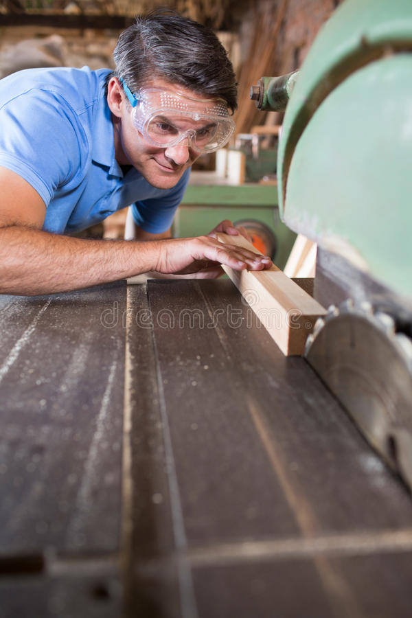 Carpenter Cutting Wood On Circular Saw royalty free stock photography