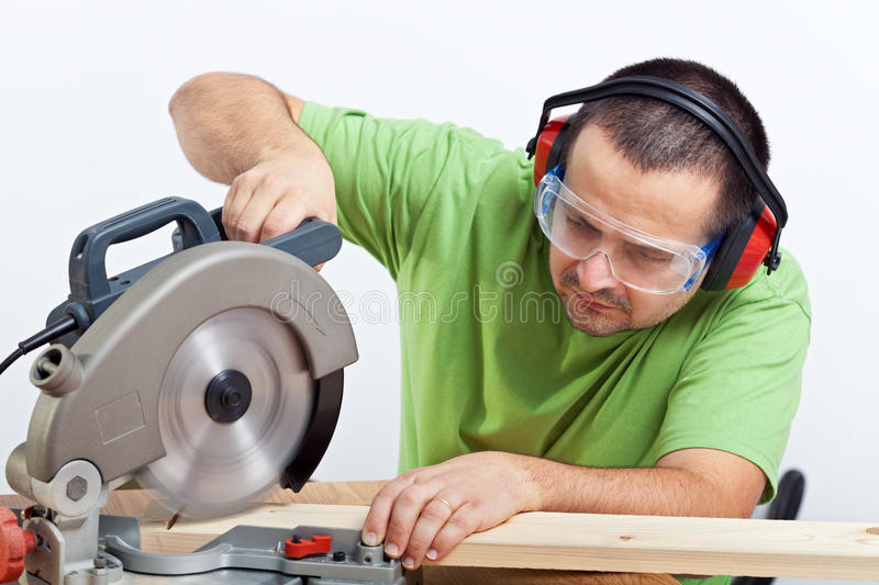 Carpenter cutting wooden plank royalty free stock photography
