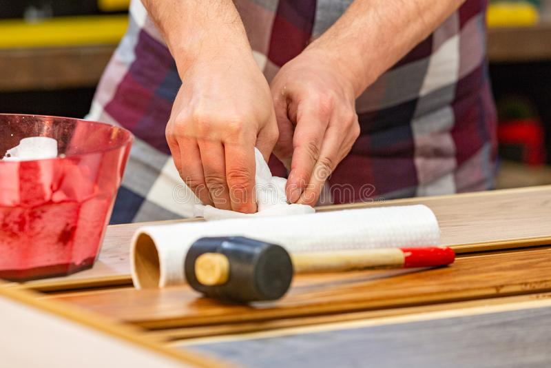 Carpenter doing his job in carpentry workshop. a man in a carpentry workshop cleans the table from the cement slurry. Carpenter doing his job in carpentry stock photography