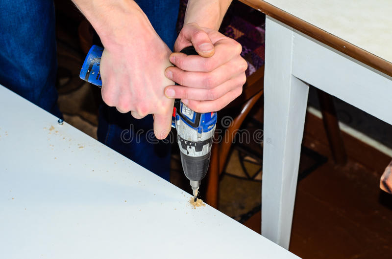 Carpenter drilling a hole in a chipboard. Carpenter drilling a hole in a white chipboard royalty free stock photography