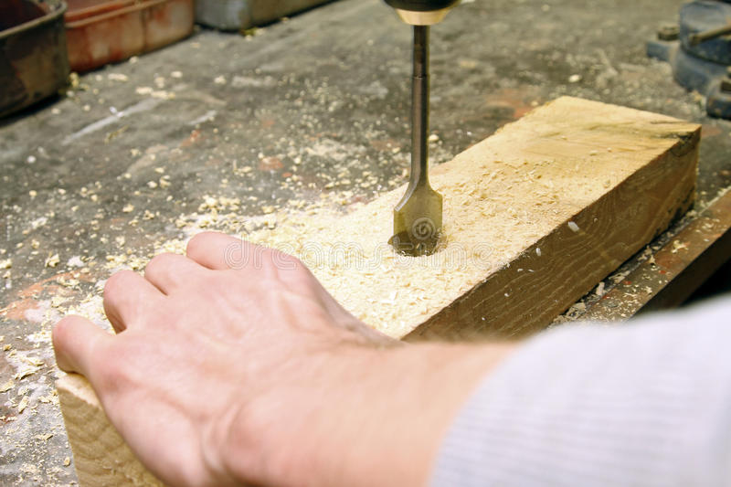 Carpenter drilling hole in a wooden board royalty free stock photo