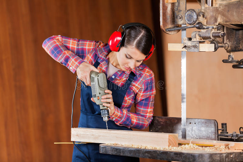 Carpenter Drilling Wood At Bandsaw. Young female carpenter using drill machine on wood at bandsaw in workshop stock photo