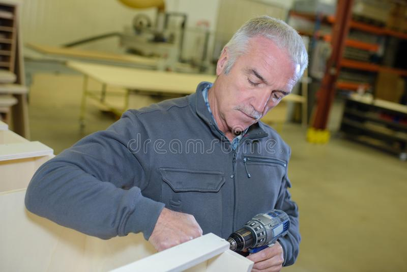 Carpenter drilling the wood royalty free stock image