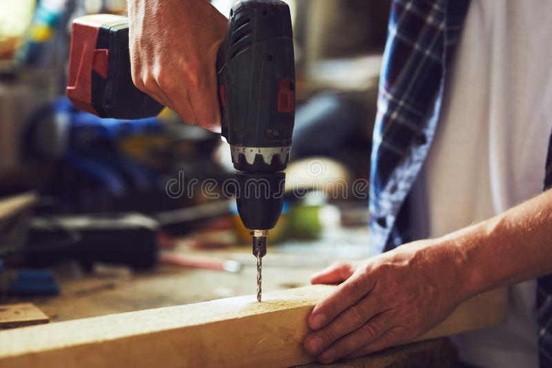 Carpenter drills a hole with an electric drill into a wooden board stock image