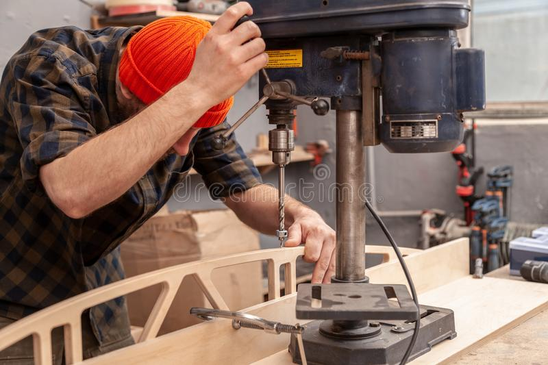Experienced carpenter work in workshop. Carpenter drills a hole with an electrical drill in wooden board. Wood boring drill in hand drilling hole in wooden bar royalty free stock images