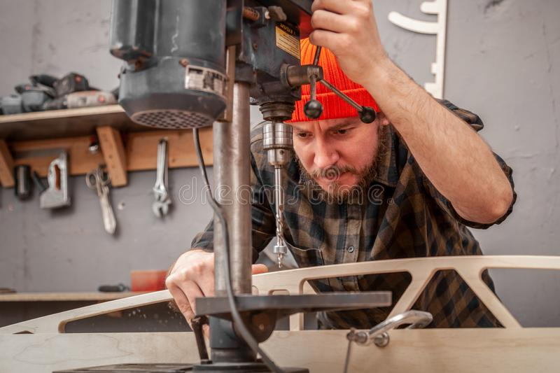 Handicraft Carpentry. Carpenter drills a hole with an electrical drill in wooden board. Wood boring drill in hand drilling hole in wooden ba royalty free stock images