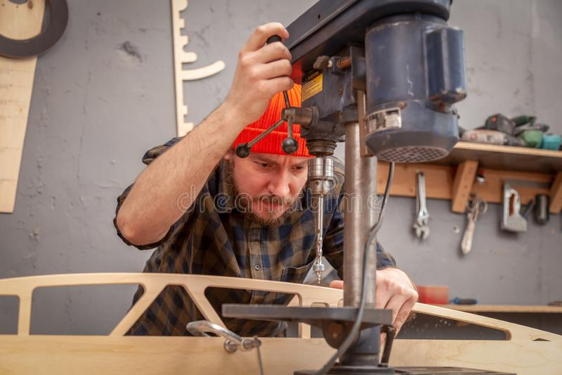 Handicraft Carpentry. Carpenter drills a hole with an electrical drill in wooden board. Wood boring drill in hand drilling hole in wooden ba royalty free stock photos