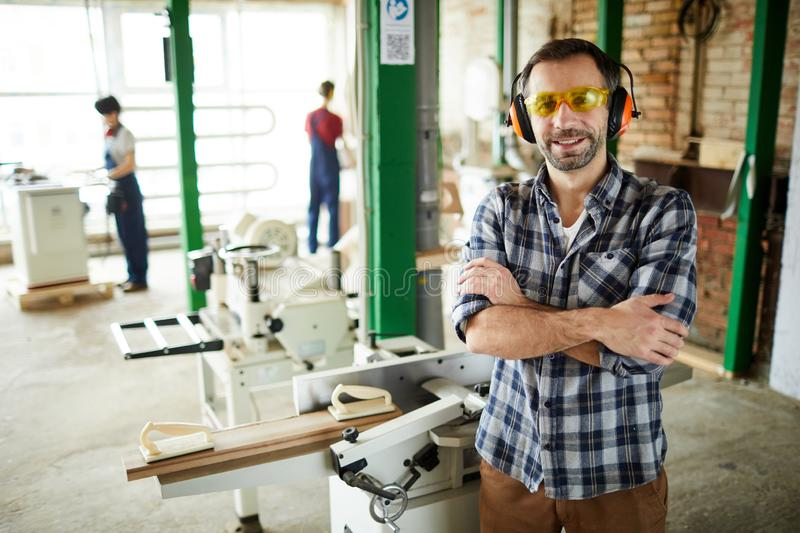 Carpenter in ear protectors standing against cutting machine. Cheerful handsome middle-aged carpenter in ear protectors and safety goggles standing against royalty free stock image