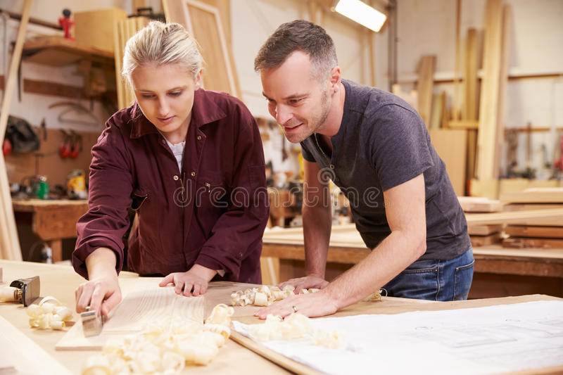 Carpenter With Female Apprentice Planing Wood In Workshop royalty free stock image