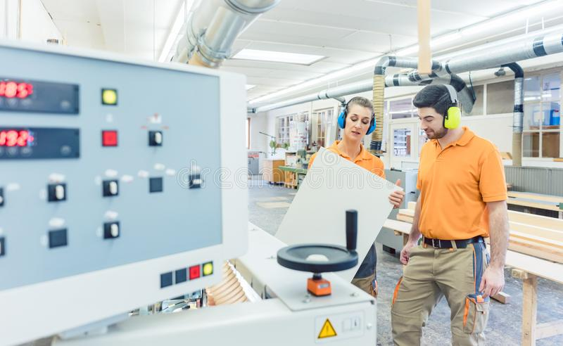 Carpenter in furniture factory inspecting piece in QA royalty free stock photos