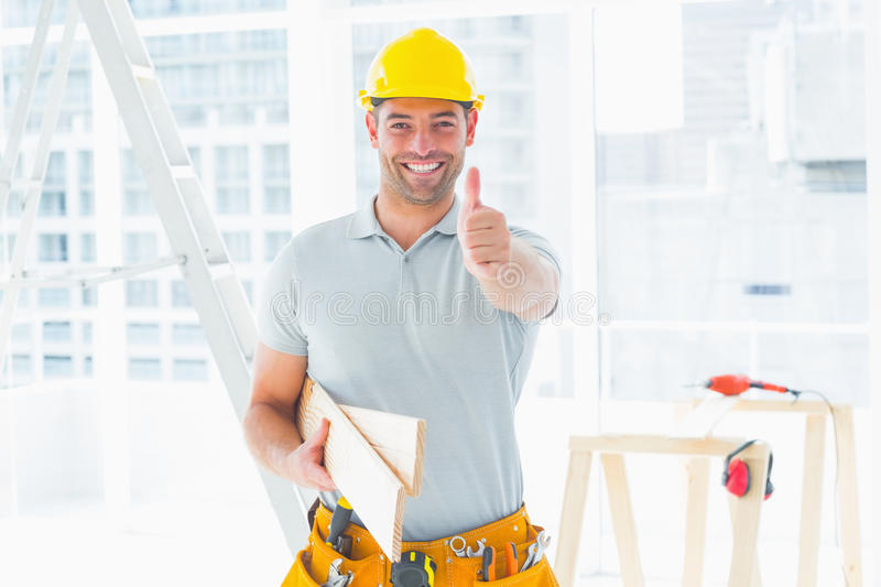 Carpenter gesturing thumbs up at construction site stock photo