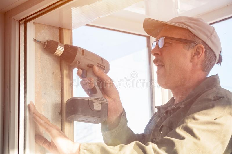 Carpenter in glasses with a drill stock image