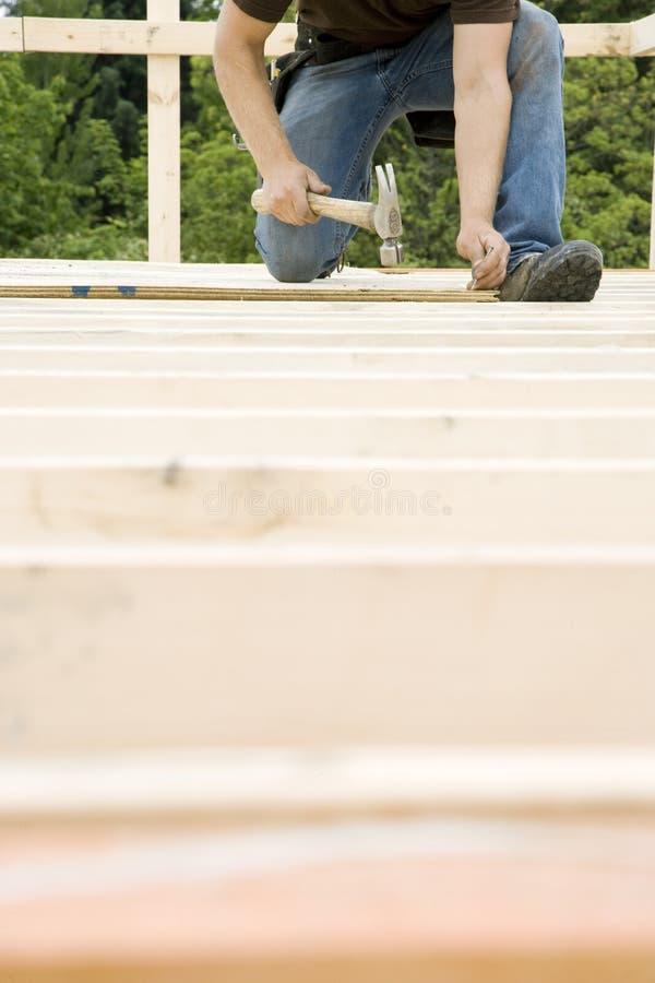 Carpenter Hammering Nail into Deck. A carpenter is hammering a nail into a deck. Vertically framed shot royalty free stock photography
