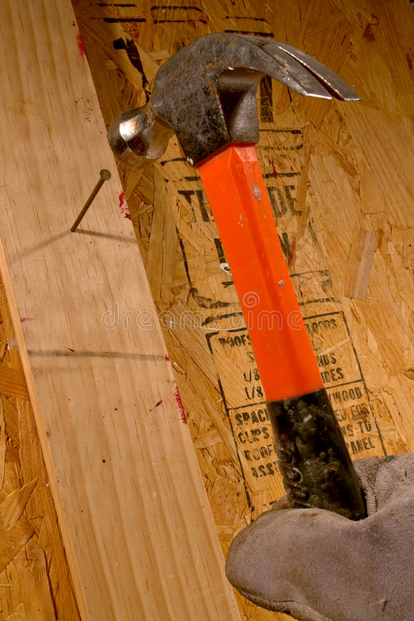 Carpenter Hand Nailing with a Construction Hammer stock images