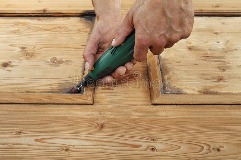 Carpenter hand work the wood with the rotary tool. On large wooden door royalty free stock photo