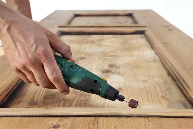 Carpenter hand work the wood with the rotary tool. On large wooden door royalty free stock images