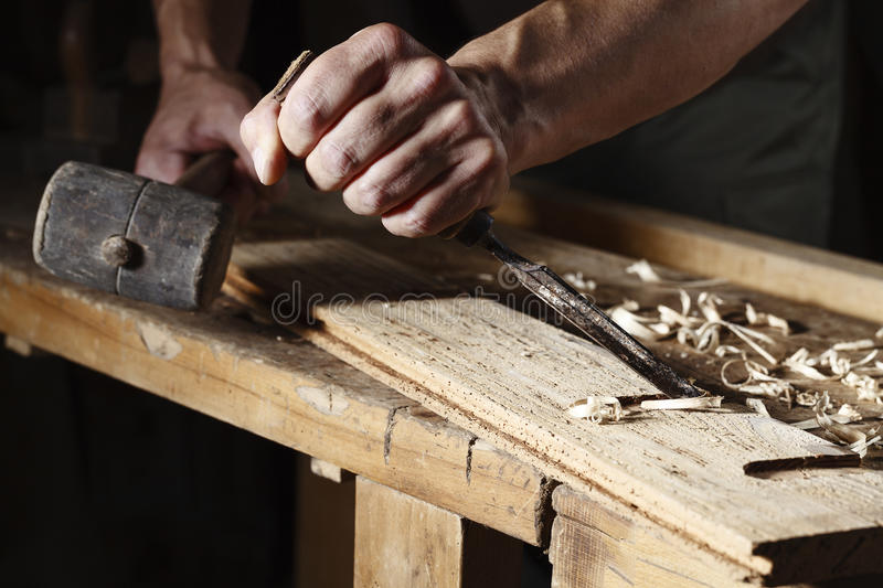 Carpenter hands working with a chisel and hammer. Closeup of a carpenter hands working with a chisel and hammer on wooden workbench stock photo