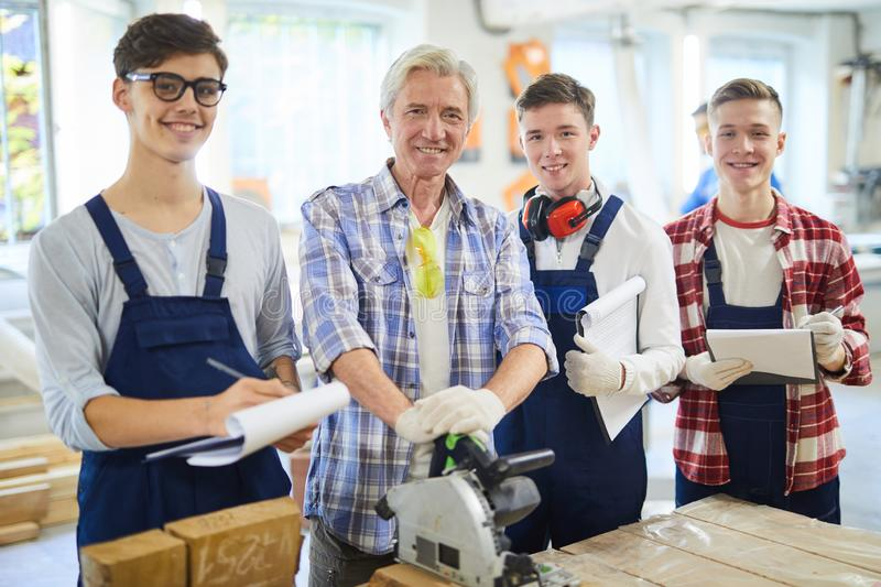 Carpenter and his students in workshop stock image