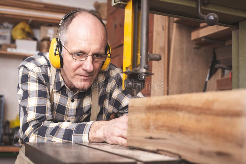 A mature carpenter using a bandsaw. A carpenter in his 50th is working on a bandsaw. He is cutting a piece of wood while wearing ear protectors, a light apron royalty free stock photos