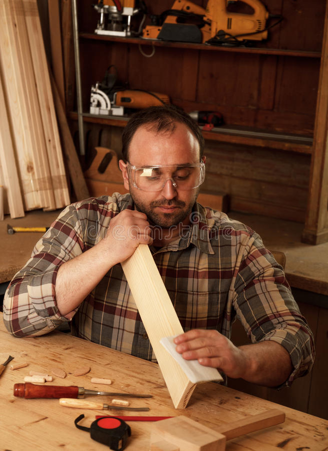 Carpenter in his workshop. Young carpenter sending piece of timber with sandpaper in his workshop royalty free stock photos