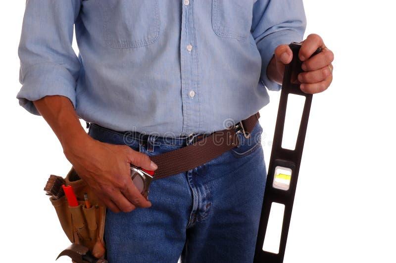 Carpenter holding level stock photo