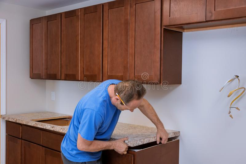 Carpenter installing c counter top in a kitchen royalty free stock image