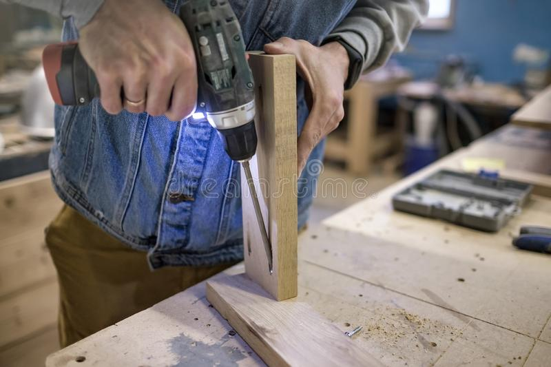 Carpenter installs the furniture hinge. Pocket hole joinery concept. stock photography