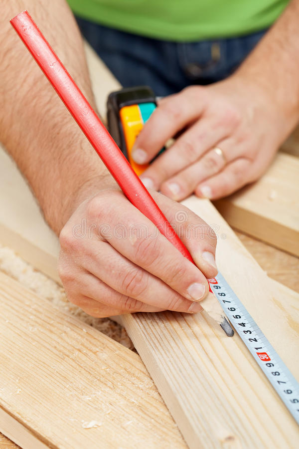 Carpenter or joiner measuring wood royalty free stock images