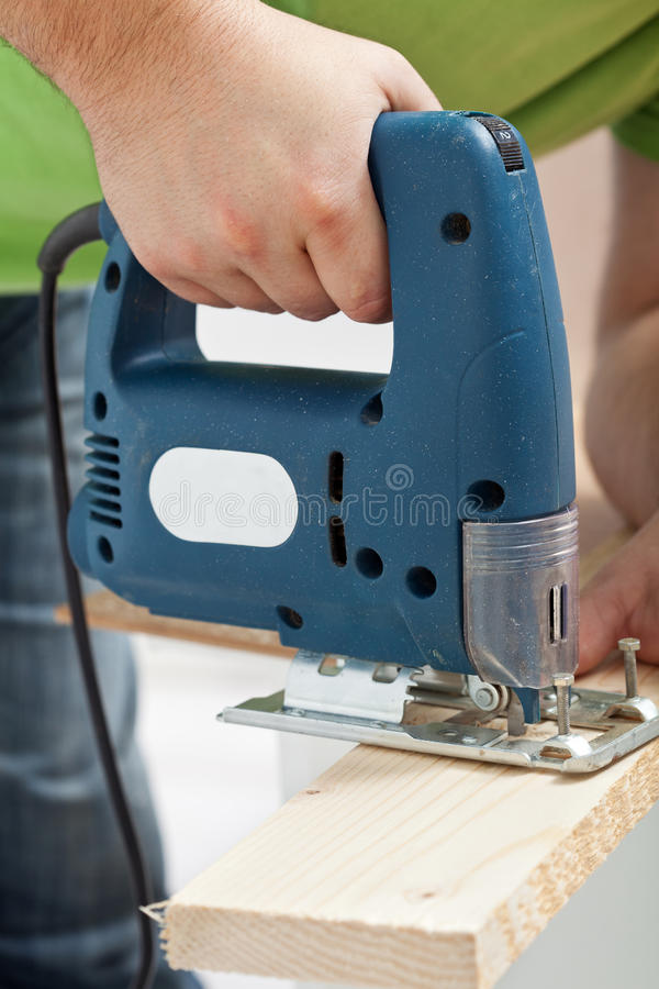 Carpenter or joiner working with electric saw stock photo