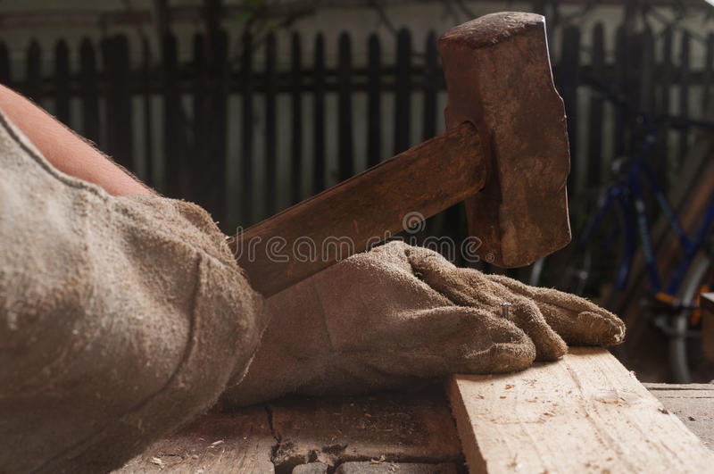 Carpenter knocking a nail into wood using hammer stock photo