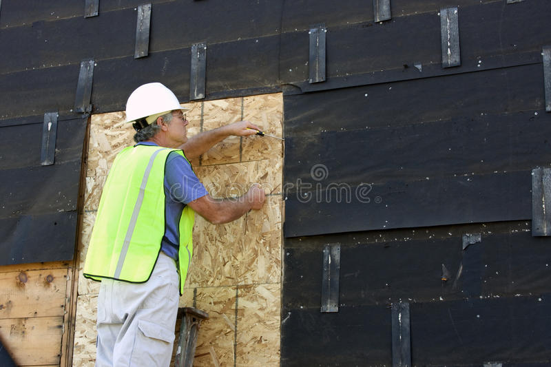 Carpenter on a ladder. Doing construction to a house stock image