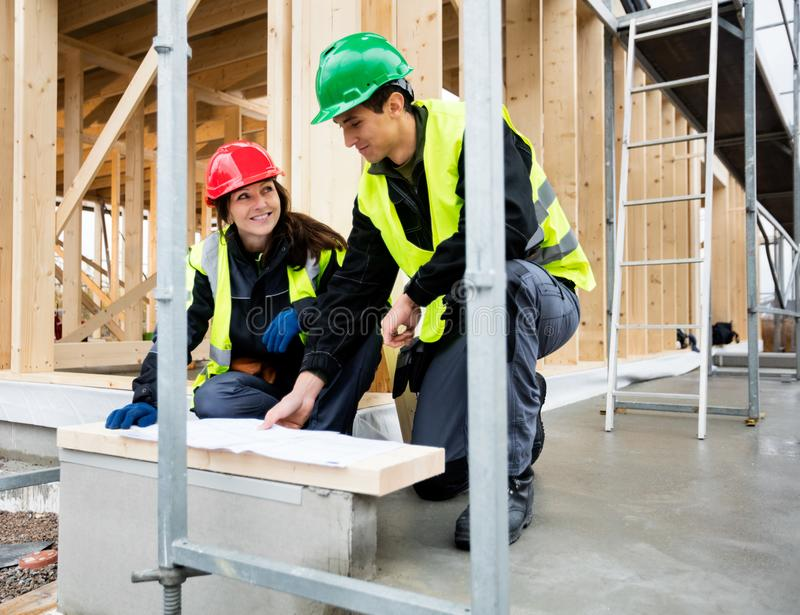 Carpenter Looking At Colleague While Discussing Plan Outside Inc. Smiling female carpenter looking at colleague while discussing plan outside incomplete building royalty free stock photography