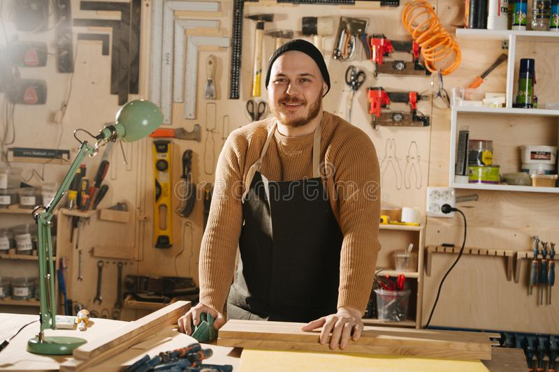 Carpenter is making furniture on order in a workshop royalty free stock photo