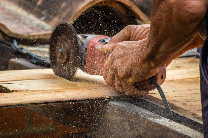 Closeup of Carpenter Working on its Woods. A Carpenter Man Cutting a Piece of Wood for Roofing Work royalty free stock photography