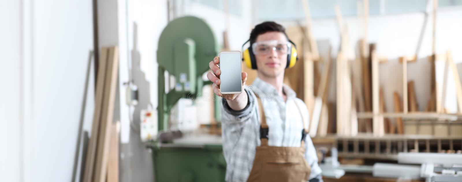 Carpenter man show the mobile phone isolated on carpentry background royalty free stock images